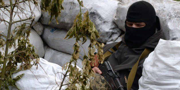 An armed pro-Russian fighter takes position at a checkpoint near the eastern Ukranian city of Slavyansk on May 12, 2014. Russ