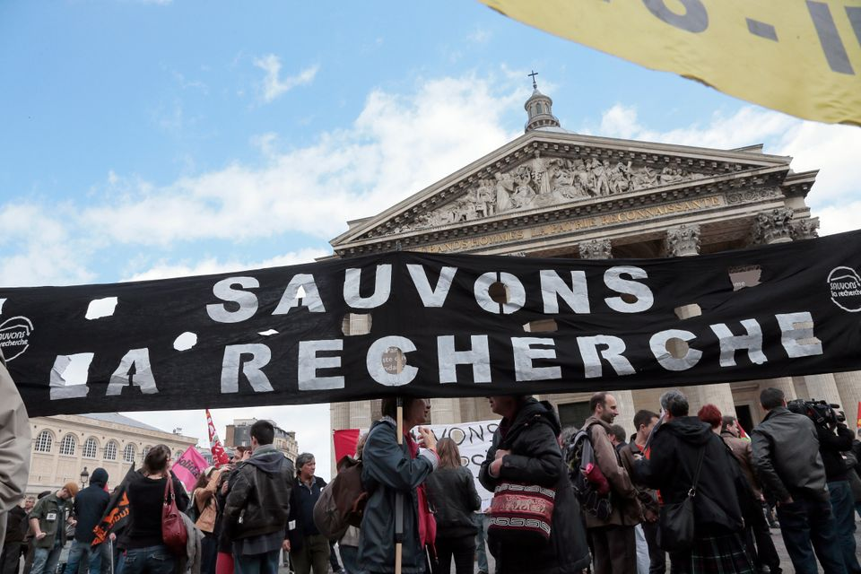 Demonstrators hold a banner reading 'Let's save research' at the Pantheon square on May 22, 2013 in Paris, during a protest a