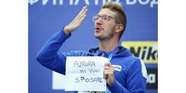 La proposta di matrimonio di Simone Ruffini medaglia d'oro di nuoto, dal podio con un cartello