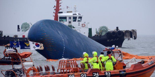 Coast guard members search for passengers near a South Korean ferry (C) that capsized on its way to Jeju island from Incheon,