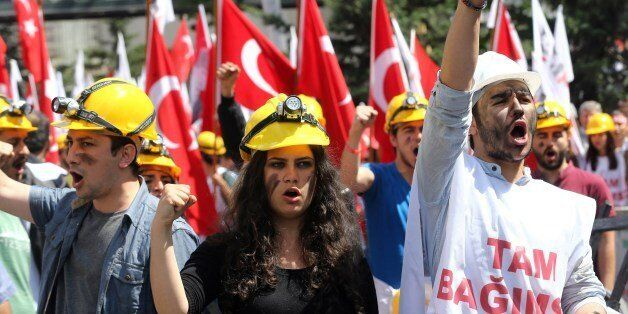 Protesters wearing hard hats raise their fists during a demonstration by the leftist Turkish Youth Union to protest the 301 d