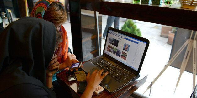 TEHRAN, IRAN - OCTOBER 13: Two girls sit in a north Tehran coffee shop using Facebook and looking on the mobile phone at onli
