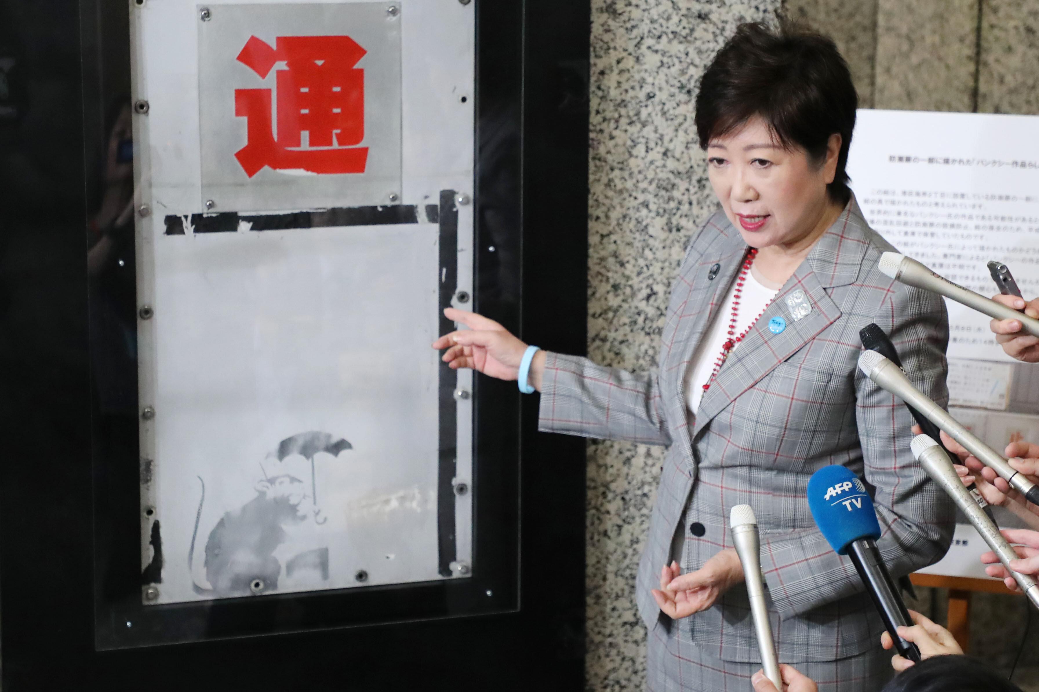 東京都庁で展示が始まったバンクシーの作品に似たネズミの絵。小池百合子知事も様子を見に来た=4月25日、東京都新宿区