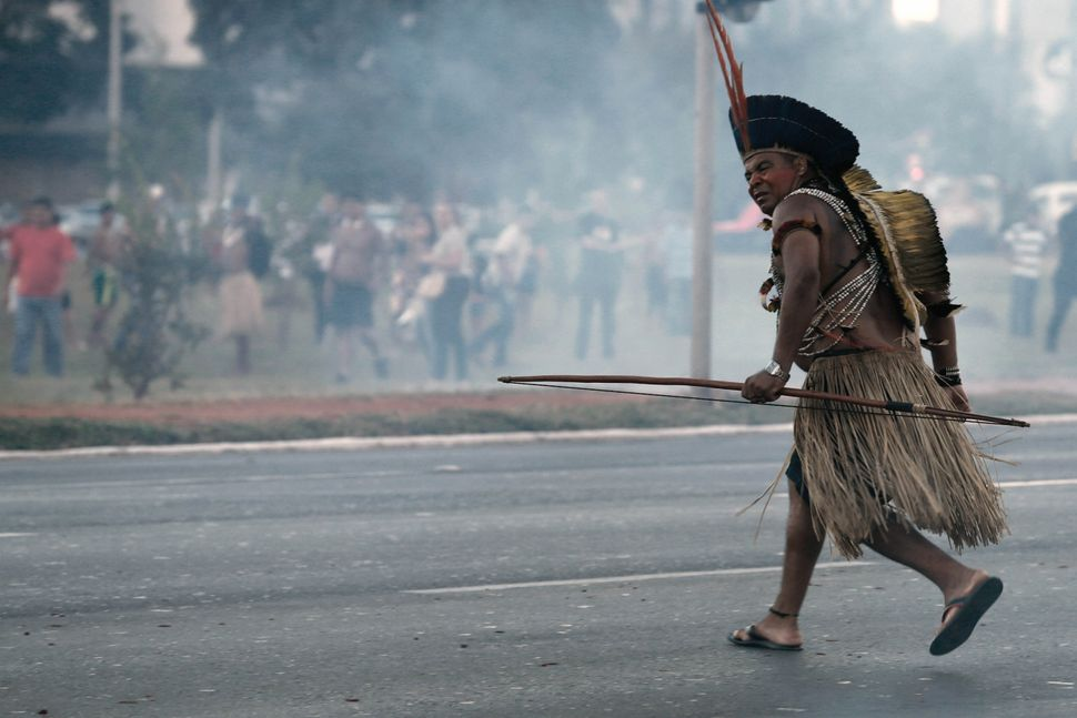 An indigenous protester runs with his bow during a protest against the World Cup outside the National Stadium in Brasilia, Br