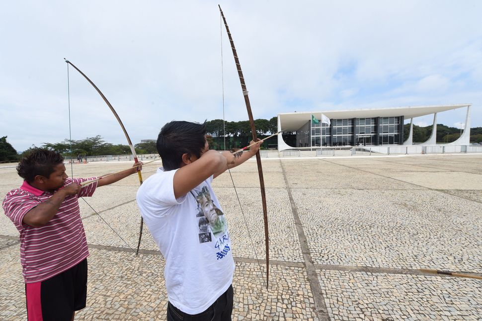 Indigenous Brazilians aim their bows at the Planalto palace during a protest in Brasilia on May 27, 2014. (EVARISTO SA/AFP/Ge