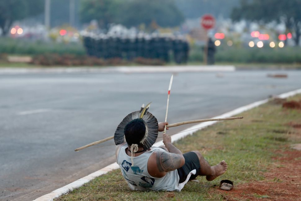 An Indigenous protester in traditional headdress gets ready to fire an arrow against the military police during a protest aga