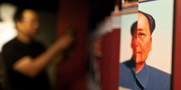 A visitor takes a photo of an exhibit showing the portrait of the late Chinese leader Mao Zedong (R) during the opening of th