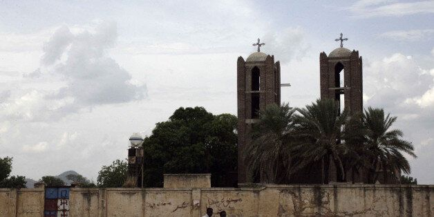 Two Sudanese youths ride their motorcycle past a church in Kadugli, the capital of Sudan's war-torn South Kordofan state, on