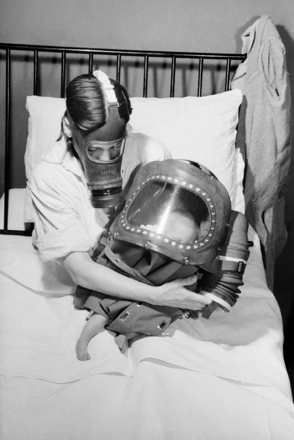 A mother cradles her newborn baby in bed, shortly after giving birth in 1941. The mother is wearing her civilian respirator,