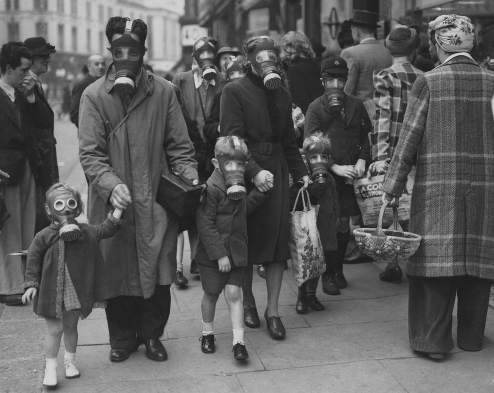 A family wearing their gas masks to the shops during a gas drill in Richmond, Surrey, May 31, 1941. The drill involved a cani
