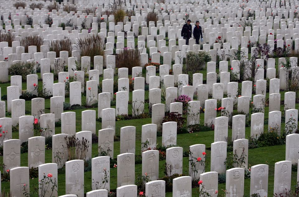 People walk among headstones in the Tyne Cot Cemetery, the largest Commonwealth war grave cemetery in the world, on November