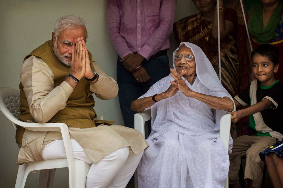 AHMEDABAD, INDIA - MAY 16: BJP leader Narendra Modi (L) gestures to supporters as he sits with his mother Heeraben Modi on he