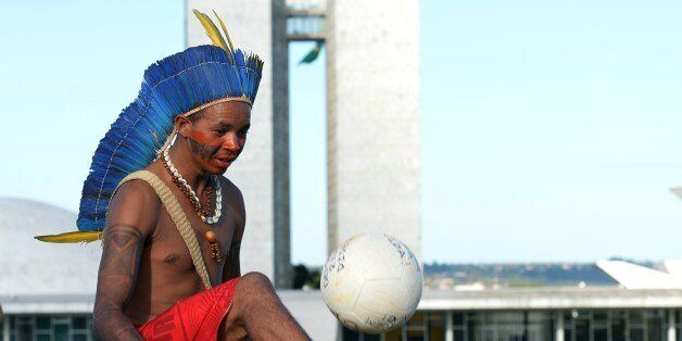 A Brazilian native plays football during a protest in front of the National Congress as part of Indigenous Mobilization Week,