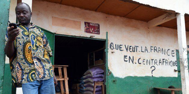 A Muslim shopkeeper uses a mobile phone in front of his shop bearing the inscription 'What does France want in Central Africa