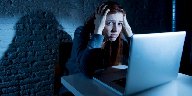 sad and scared female teenager with computer laptop suffering cyberbullying and harassment being online...