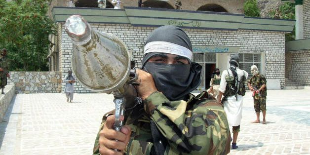 A Pakistani pro-Taliban militant carries rocket propelled granade launcher (RPG) as he stands inside the shrine in Lakaro vil