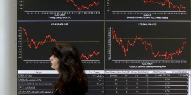 An employee of the Stock Exchange passes a display showing stock price movements in Athens, Wednesday,...