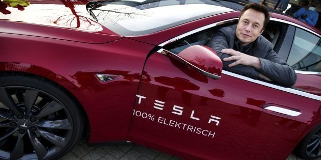 Elon Musk, co-founder and CEO of American electric vehicle manufacturer Tesla Motors, poses with a Tesla during a visit to Am