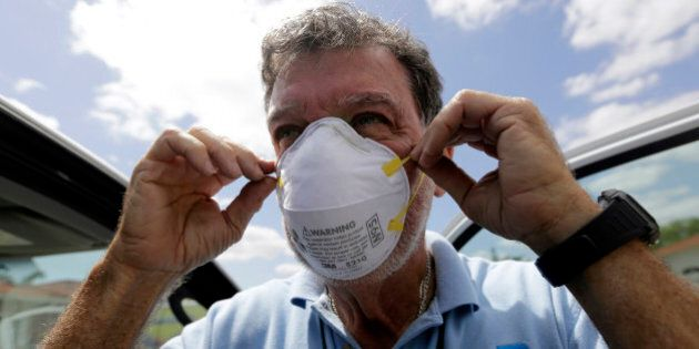 Giraldo Carratala, an inspector with the Miami-Dade County mosquito control unit, puts on a mask before...