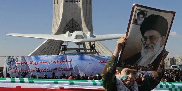 An Iranian boy holds a portrait of supreme leader, Ayatollah Ali khamenei as he walks past a replica of the captured US RQ-17