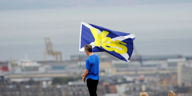 A pro-independence supporter holds a Saltire flag with 'Yes' written on it in Edinburgh on September 21, 2013 during a march