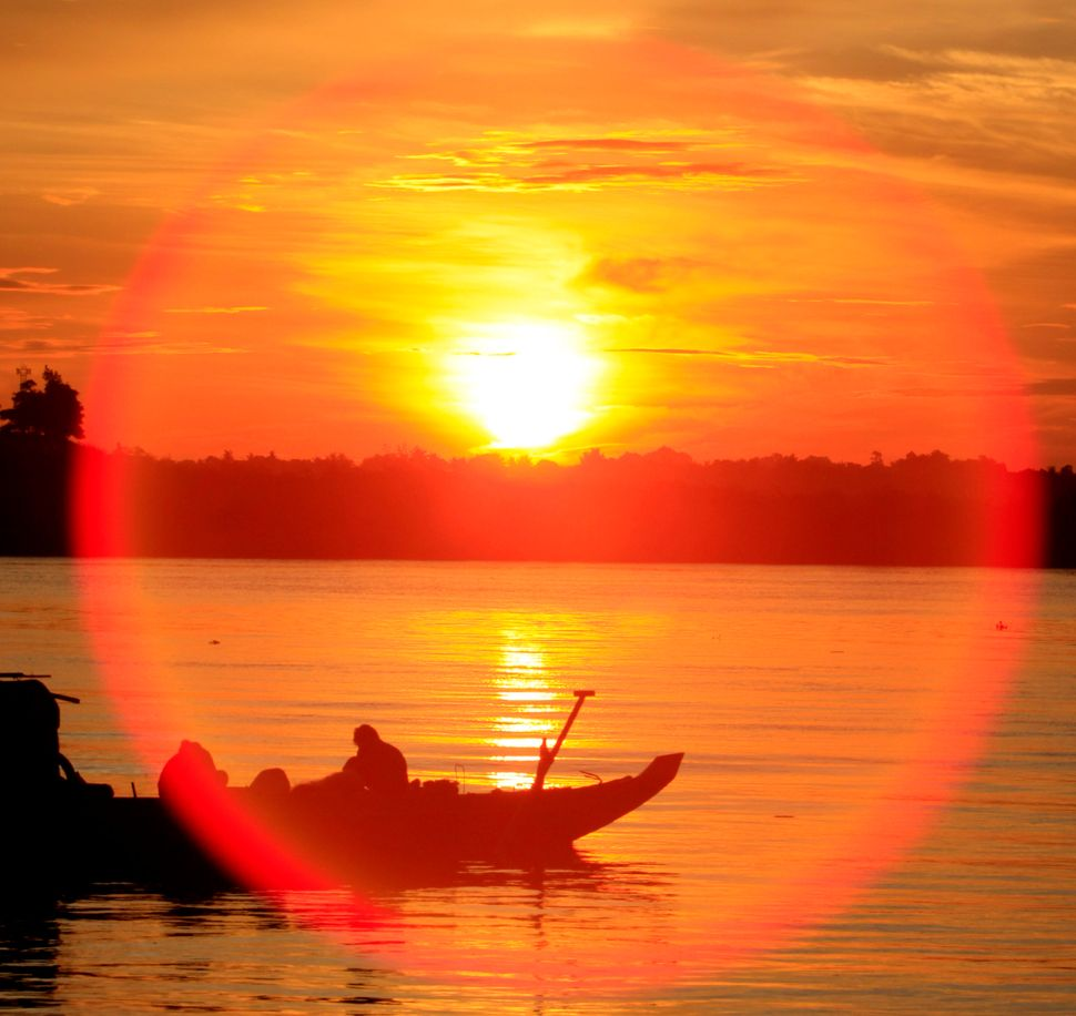 A reflection from the sunshine rises above a fishing wooden boat on the Tonle Sap river as Cambodian fishermen catching fish