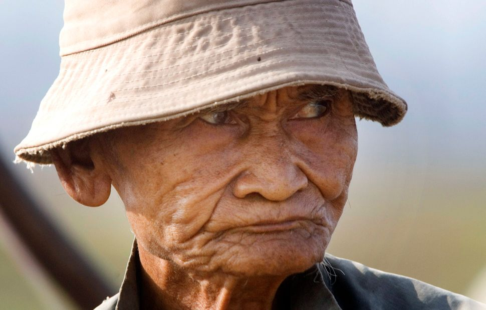 A Local Cambodian villager, Choeung Soeung, 73, looks on as his plows farm field before planting rice in Kob Srov village, ab