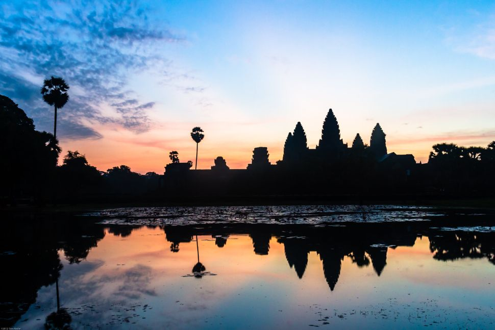 The sun rises behind the well known temple of Angkor Wat creating a silhouette of the temple against the sunrise. (Tom Roche/
