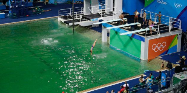 The water of the diving pool appears a murky green, in stark contrast to the pool's previous day's color...