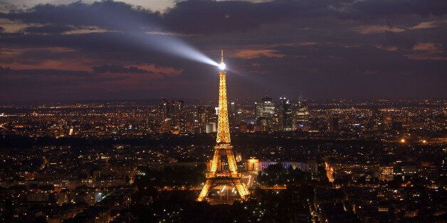 A general view shows the Eiffel Tower at night on July 14, 2012 in Paris.  AFP PHOTO / LOIC VENANCE        (Photo credit shou