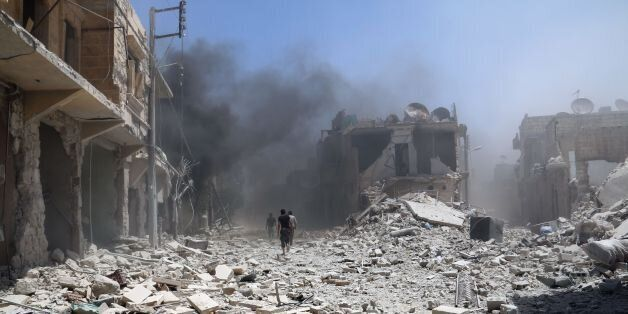 Rubble covers the street following an alleged airstrike by a Syrian army helicopter in the northern city of Aleppo, on June 1