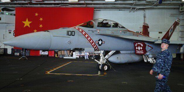 A US navy serviceman walks past an F/A-18 Hornet warplane onboard the USS George Washington, a nuclear powered aircraft carri