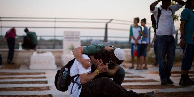 MODI'IN, ISRAEL - JULY 01:  People mourn during the funeral ceremony held for the three Israeli teenagers found dead, on July