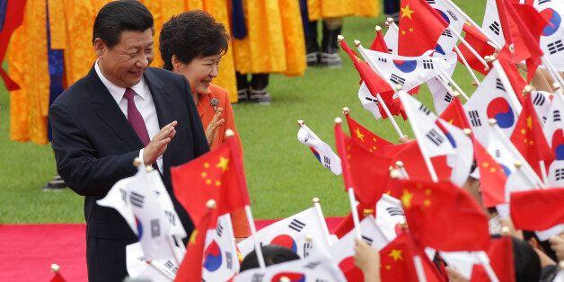 SEOUL, SOUTH KOREA - JULY 03:  Chinese President Xi Jinping and South Korean President Park Geun-Hye greet South Korean child