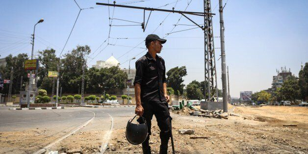 An Egyptian police officer looks on following a bomb blast in the vicinity of the Ittihadiya palace in the Egyptian capital C