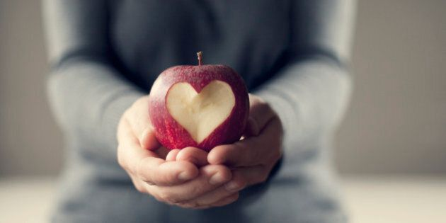 A person holding a red apple in their hands.There is a heart carved out of the