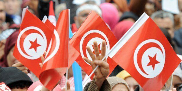 Tunisians wave their national flag and flash the four finger symbol known as 'Rabaa', which means four in Arabic, which is as