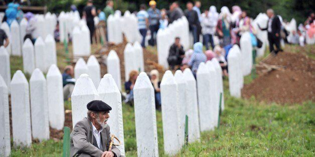 An elderly Bosnian Muslim man, survivor of the Srebrenica 1995 massacre, pays his respects at a relative's grave at the Srebr