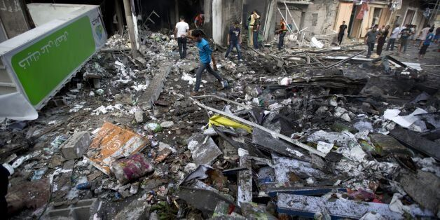 Palestinian inspect the destruction following an Israeli air strike in Gaza City on July 11, 2014. Israeli warplanes kept up