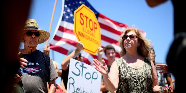 MURRIETA, CA - JULY 7:  Immigrant rights activist Mary Estrada (R) speaks with anti-immigration activists during a protest ou