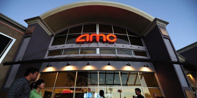 People walk past movie theaters of the US cinema chain AMC Entertainment in Monterey Park, east of downtown Los Angeles on Ma
