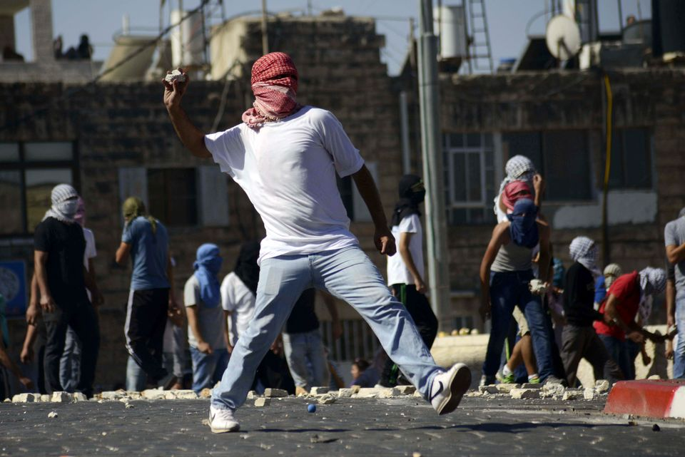 A Palestinian throws a stone during clashes with Israeli border police in Jerusalem