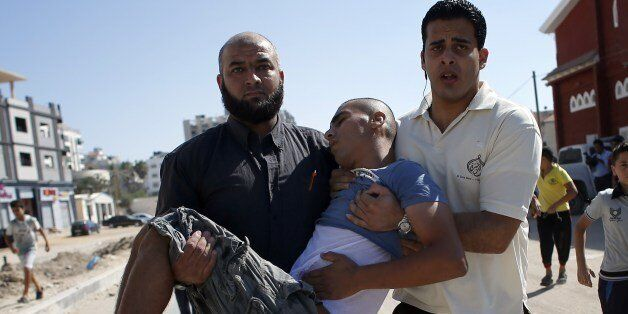 Palestinian employees of Gaza City's al-Deira hotel carry a wounded boy following an Israeli military strike nearby on the be