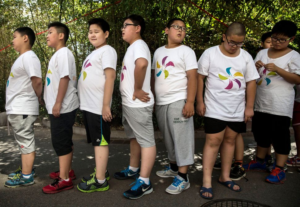 Overweight Chinese students line up before training at a camp held for overweight children on July 14, 2014 in Beijing, China