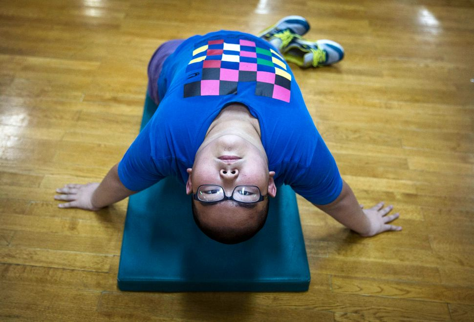 An overweight Chinese student stretches during training at a camp held for overweight children at a local university on July