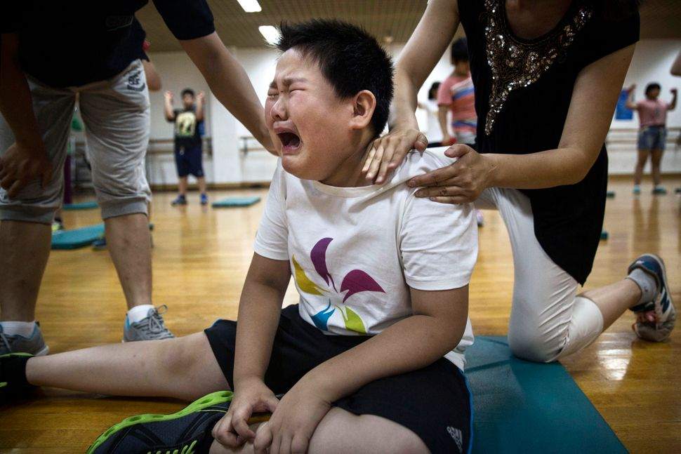 An overweight Chinese student weeps after a light exercise during training at a camp held for overweight children at a local