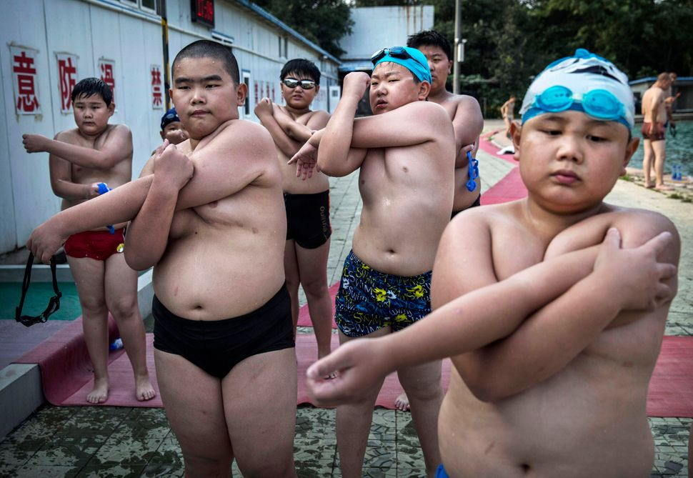 Overweight Chinese students stretch after swimming during training at a camp held for overweight children on July 15, 2014 in