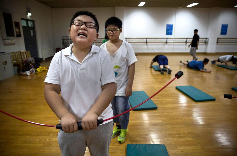 An overweight Chinese student uses a strengthening device during training at a camp held for overweight children at a local u