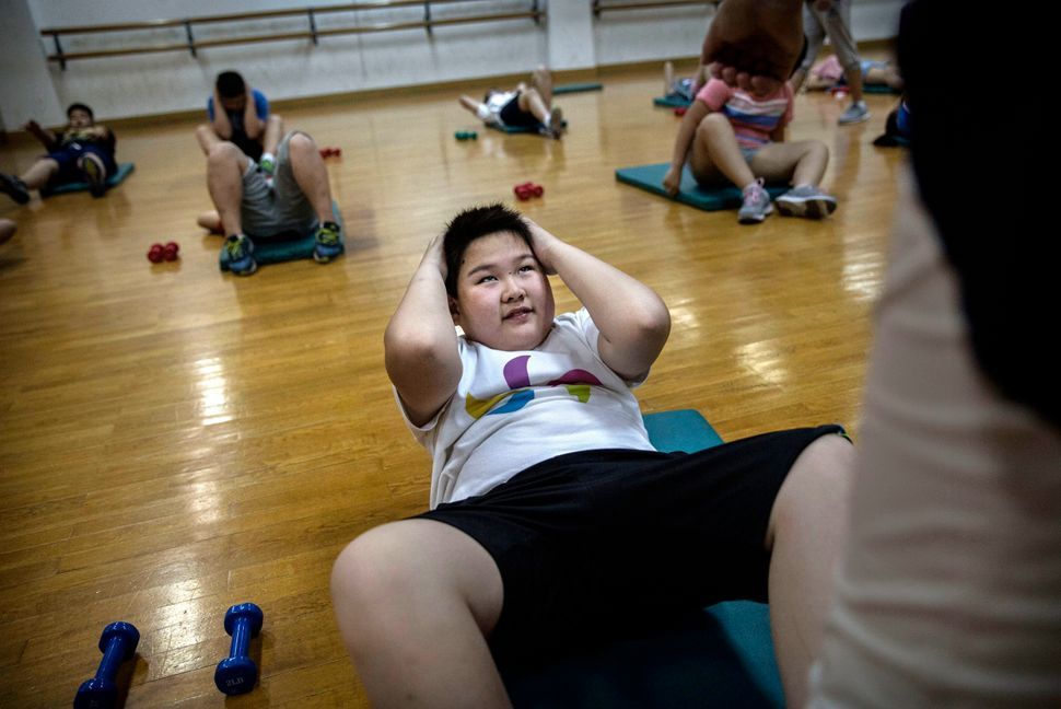 An overweight Chinese student does sit-ups during training at a camp held for overweight children at a local university on Ju