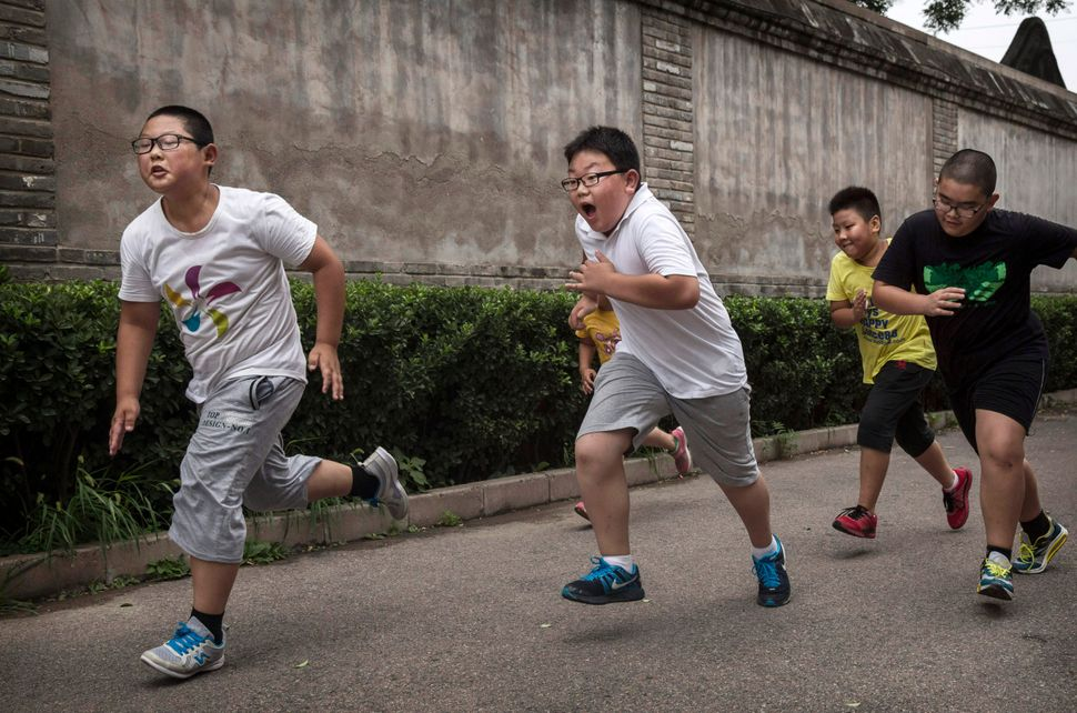 Overweight Chinese students run during training at a camp held for overweight children at a local university on July 17, 2014